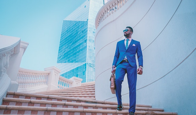 A man in a crisp blue suit holding a brown satchel walking down a white brick staircase with glass buildings in the background