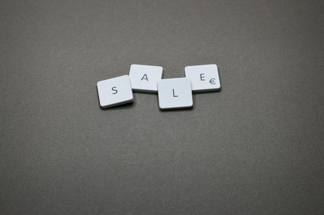 "Four white Scrabble pieces that spell ""sale."""