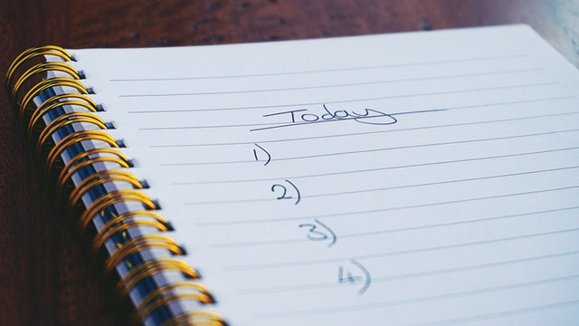"A spiral notebook with the word ""Today"" written down above an ordered list"