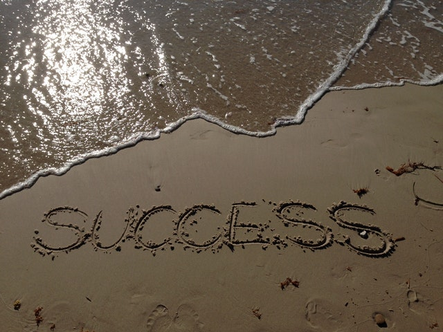 The word SUCCESS written in sand near a body of water.