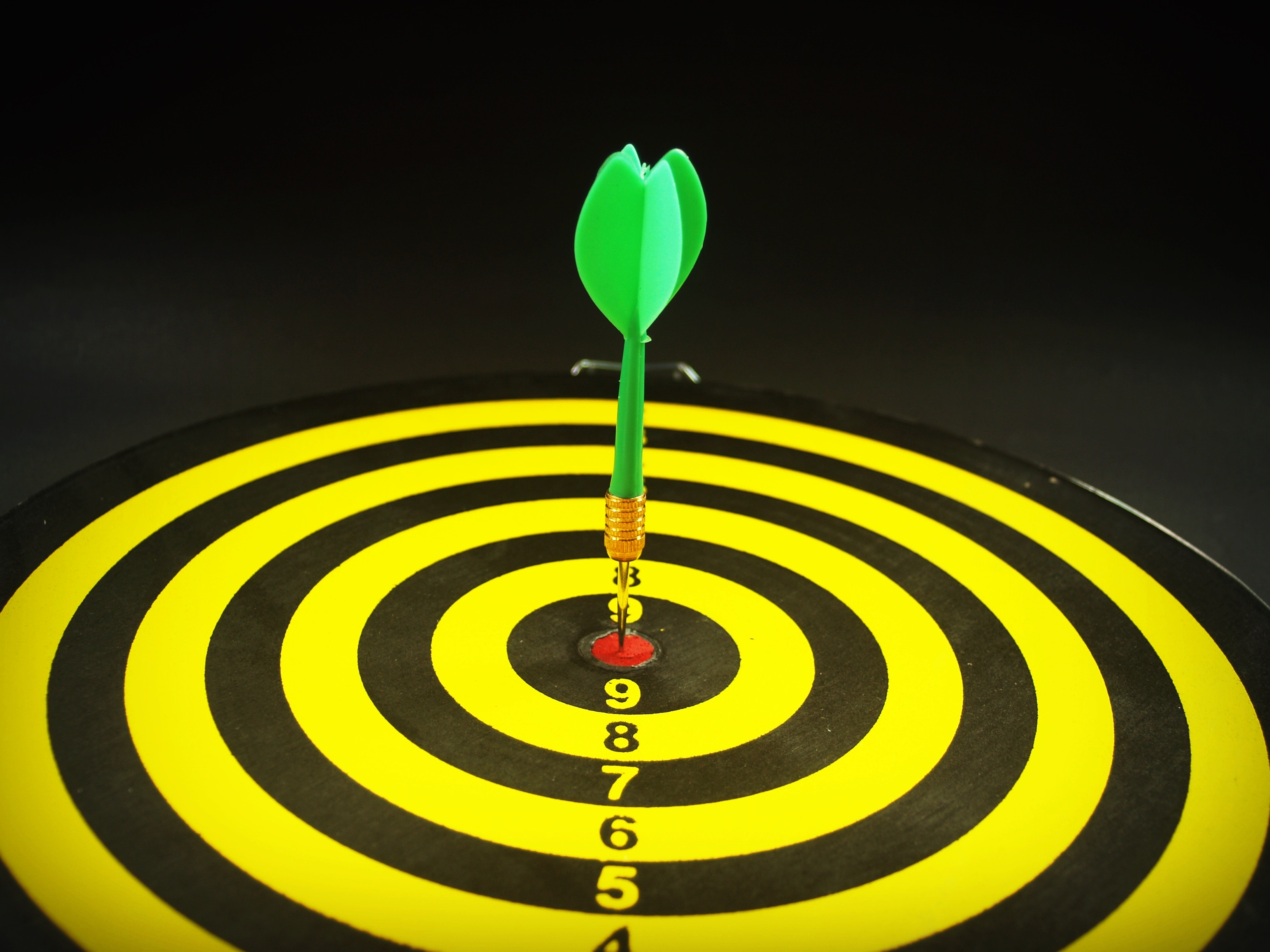 A green dart within a red bullseye on a black and yellow dartboard.