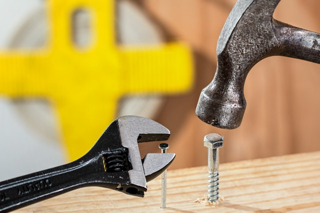 A wrench hovering over a nail and a hammer hovering over a screw, indicating a misuse of tools.