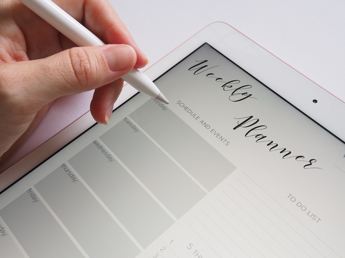 Woman holding stylus in left hand over blank Apple tablet with title Weekly Planner on it