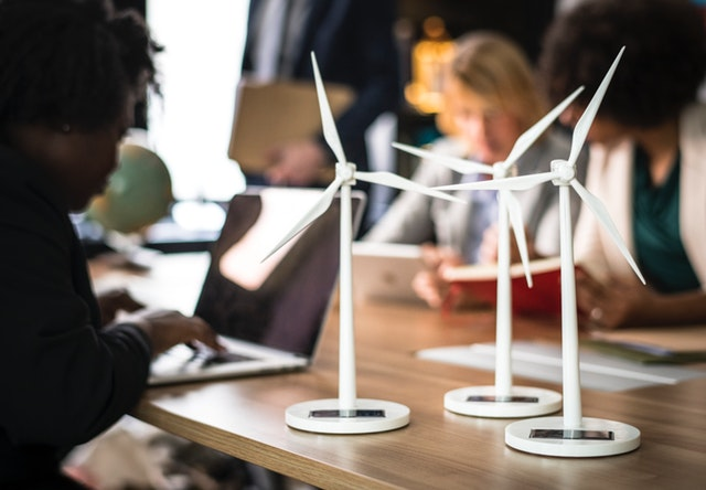 Three small, solar-powered windmills set on a long wooden table. The background is blurred, but there are people working at the table.