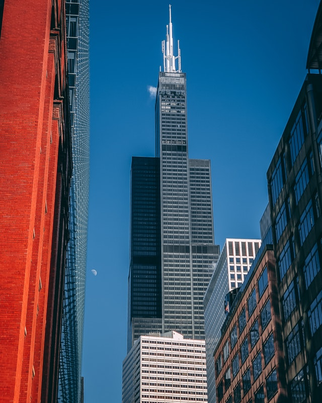 A focus shot of Chicago's Willis (or Sears) Tower, which is a huge, black-gray building, with other Chicago architecture along the periphery, including a slice of a red brick building on the left.