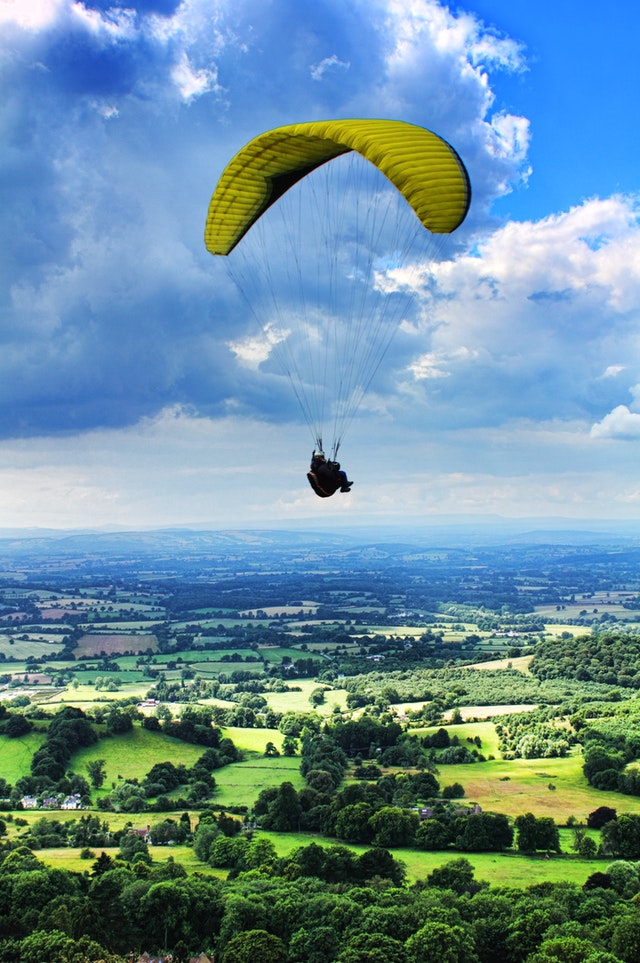 A person paragliding over a hilly landscape using a yellow parachute.
