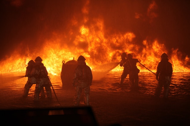Six firefighters fighting an oil fire on a dark beach.