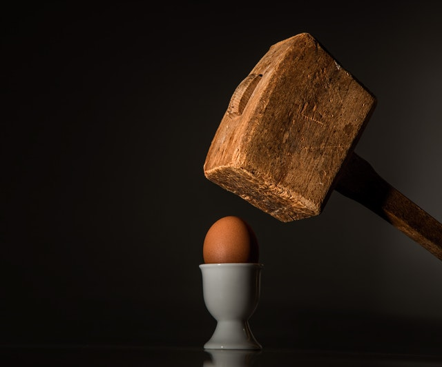 A brown egg in an egg cup with a huge wooden mallet hovering over it as if to crush the egg.