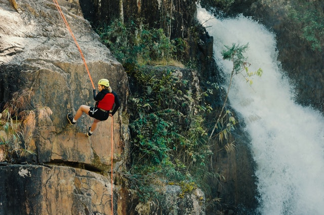 A woman climbing a steep rockface using an orange rope and climbing gear, with a large waterfall to her right.