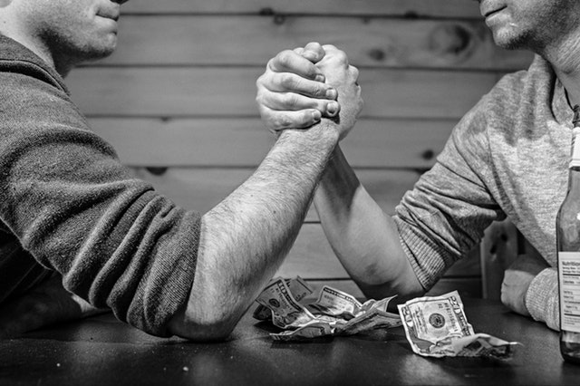 Two men arm wrestling on a wooden table with a small pile of money between them.
