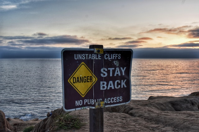 """A brown sign reading """"Unstable Cliffs, Stay Back, No Public Access"""" in front of an ocean view."""