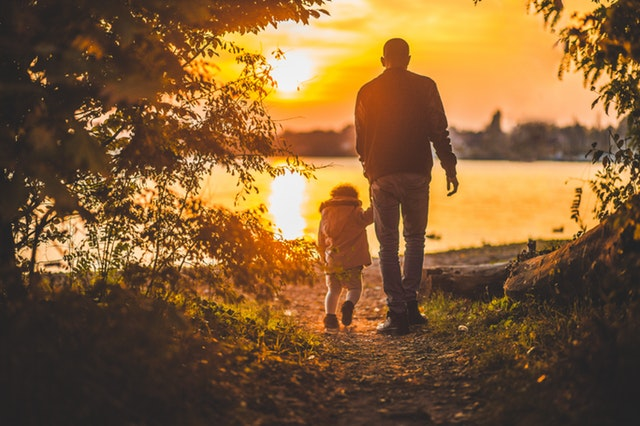 An older man holding a child's hand, walking into a sunset.