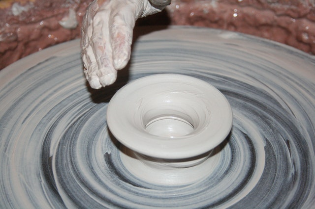 A person's hand hovering over a wet clay pot on a potter's wheel