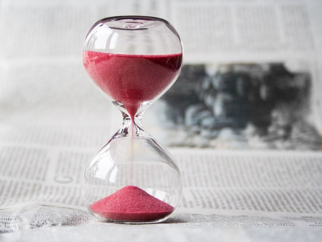 A small glass hourglass with red sand.