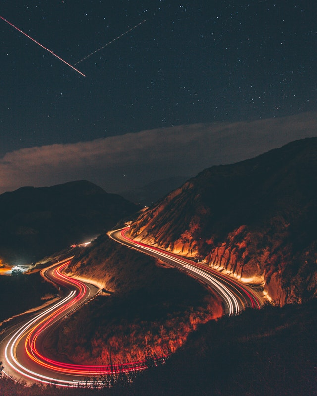 A long-exposure shot of a twisting road with smeared car lights.