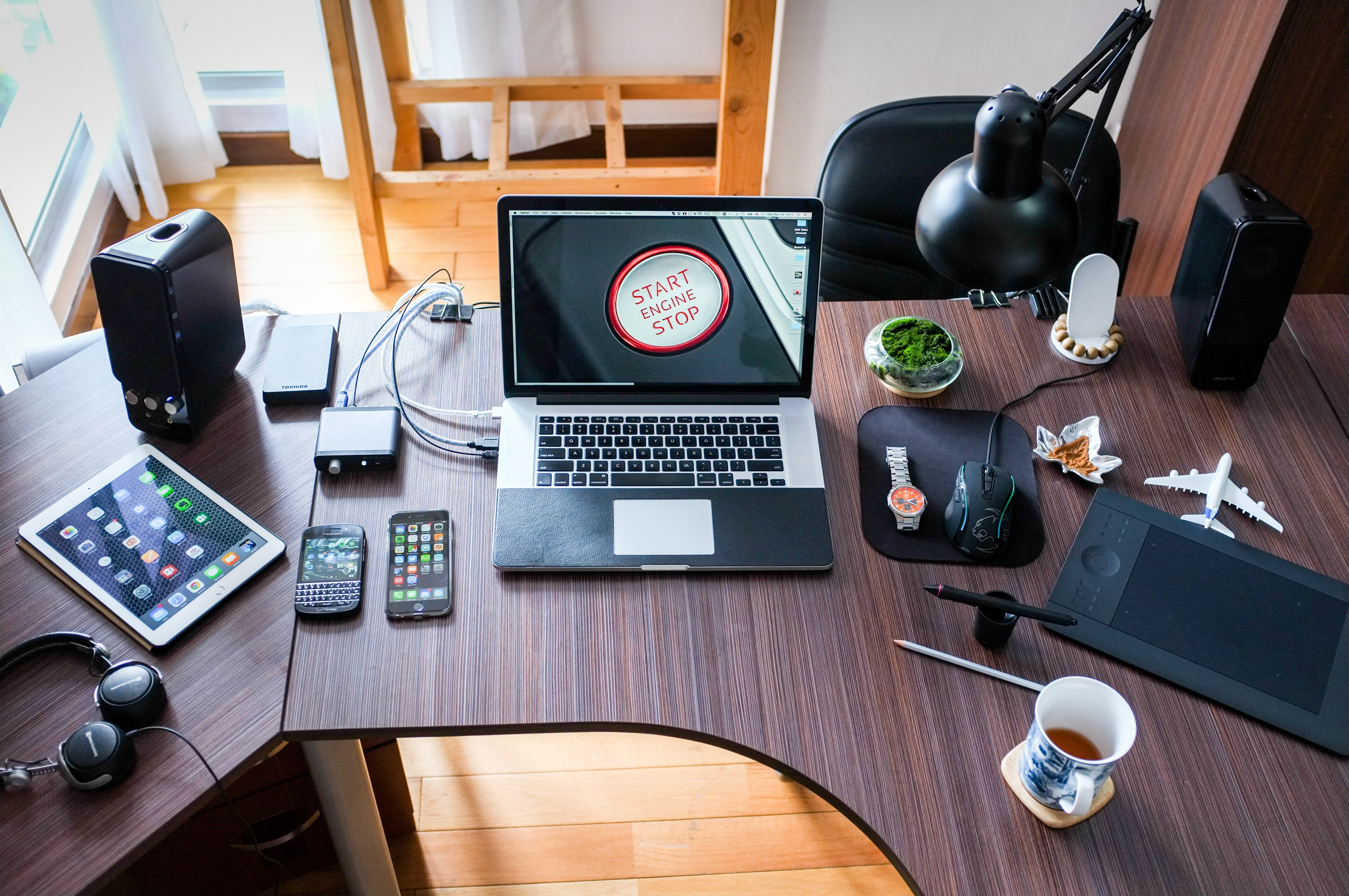 A brown, boomerang-shaped desk with a laptop, Blackberry, iPhone, tablet, gaming mouse, and cup of coffee on it in a bright room.