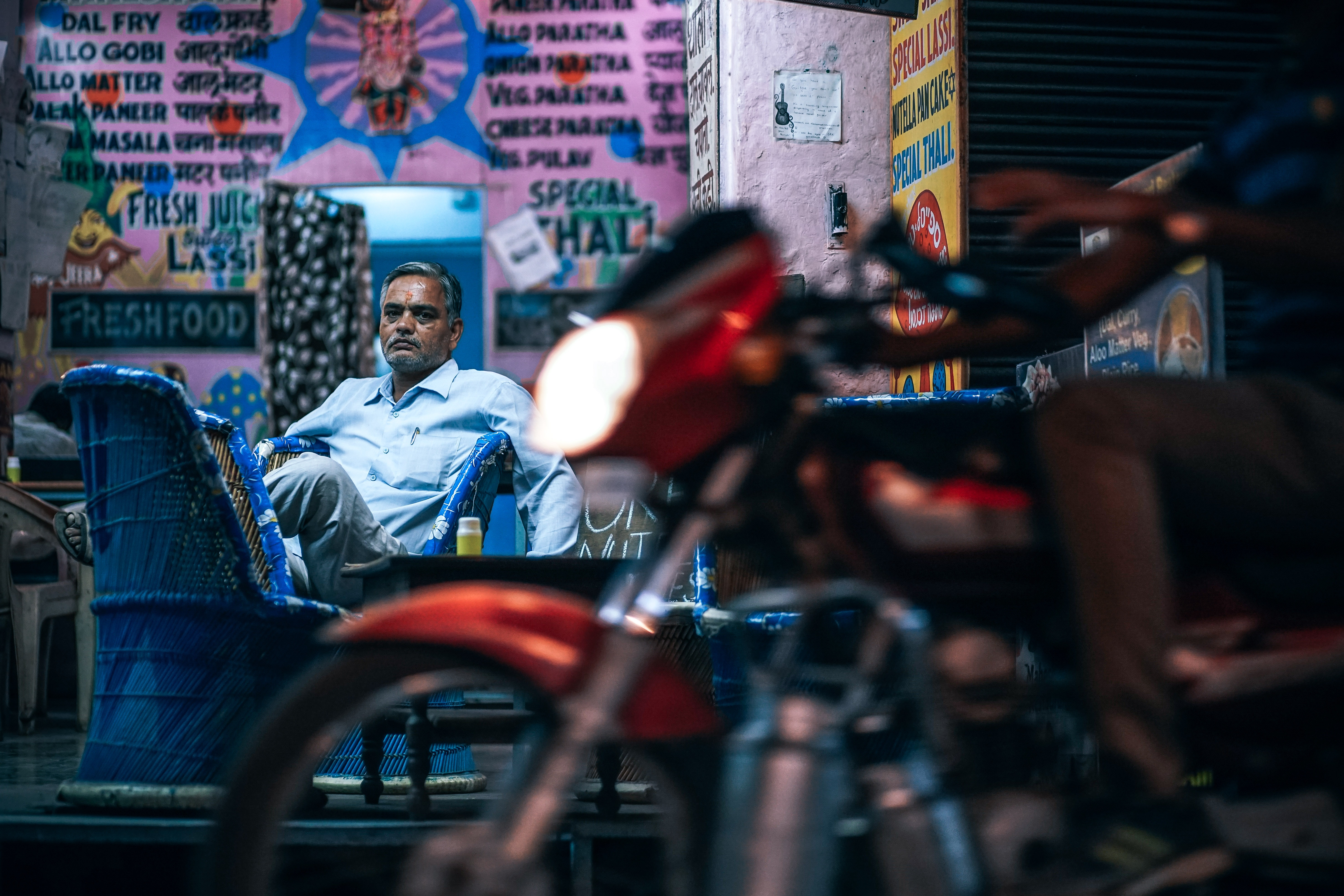 A tired, well-dressed, intensely focused man sitting in front of a food stand on a street at night, staring at an out-of-focus motorcycle in the foreground.
