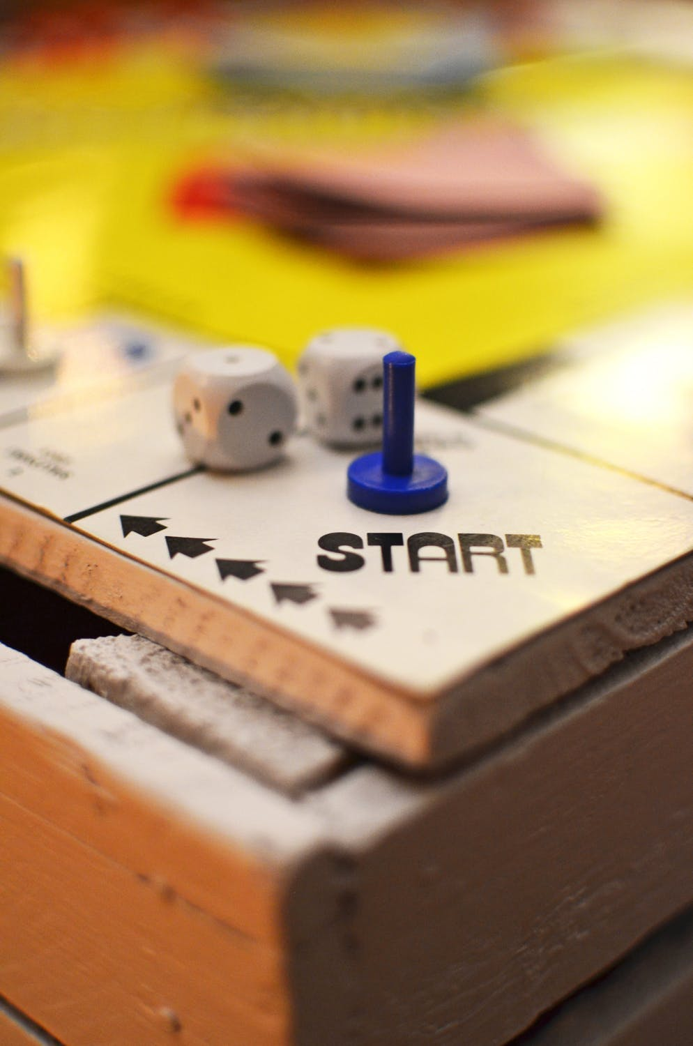 """Wooden game board with a tall blue game piece and two rounded dice on a square that says """"Start."""""""