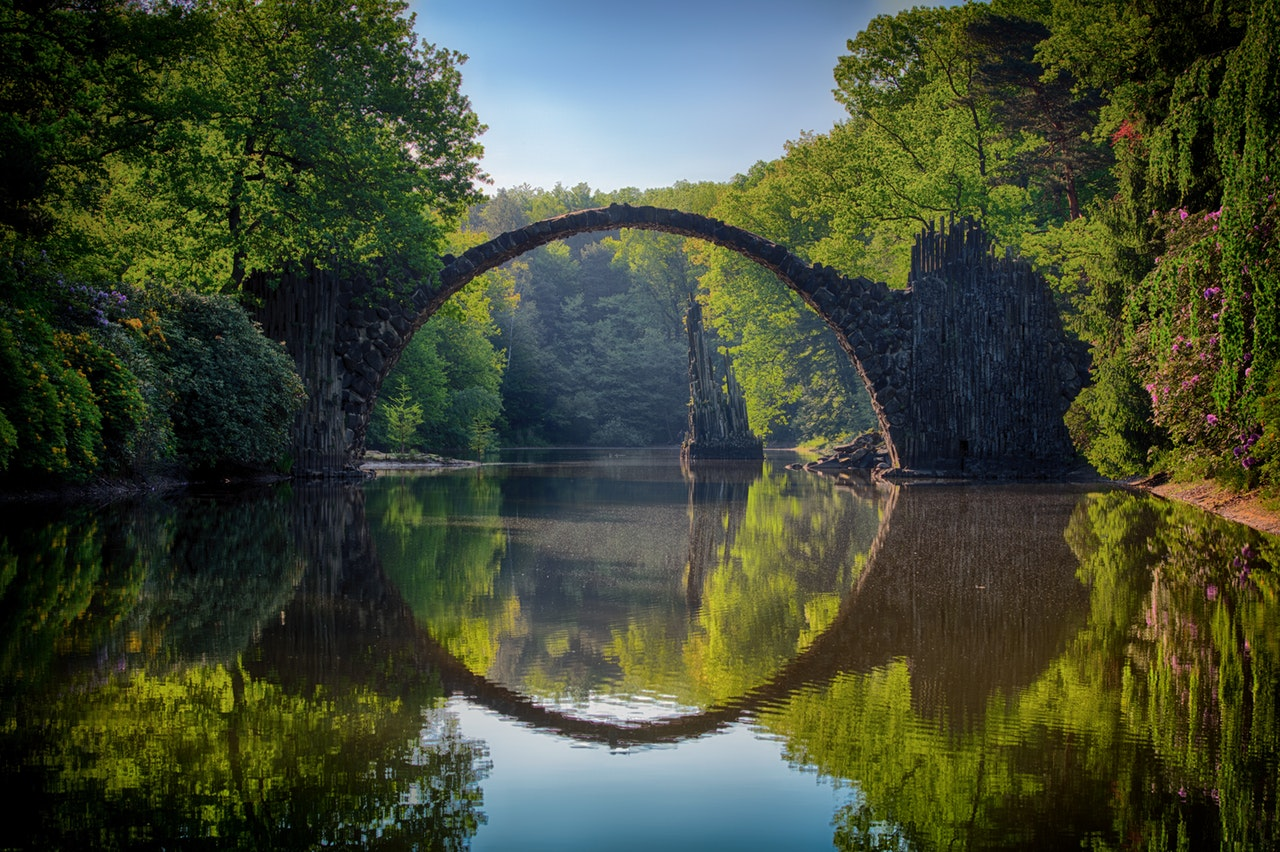 A thin stone arch bridge traversing a river surrounded by lush green trees.