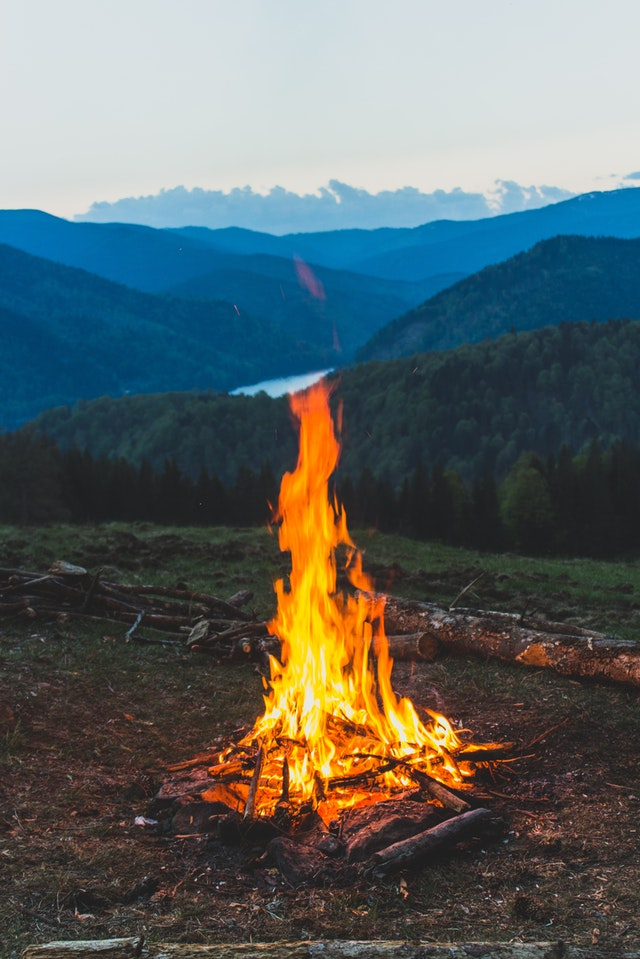 A burning bonfire in front of misty mountains at dawn.