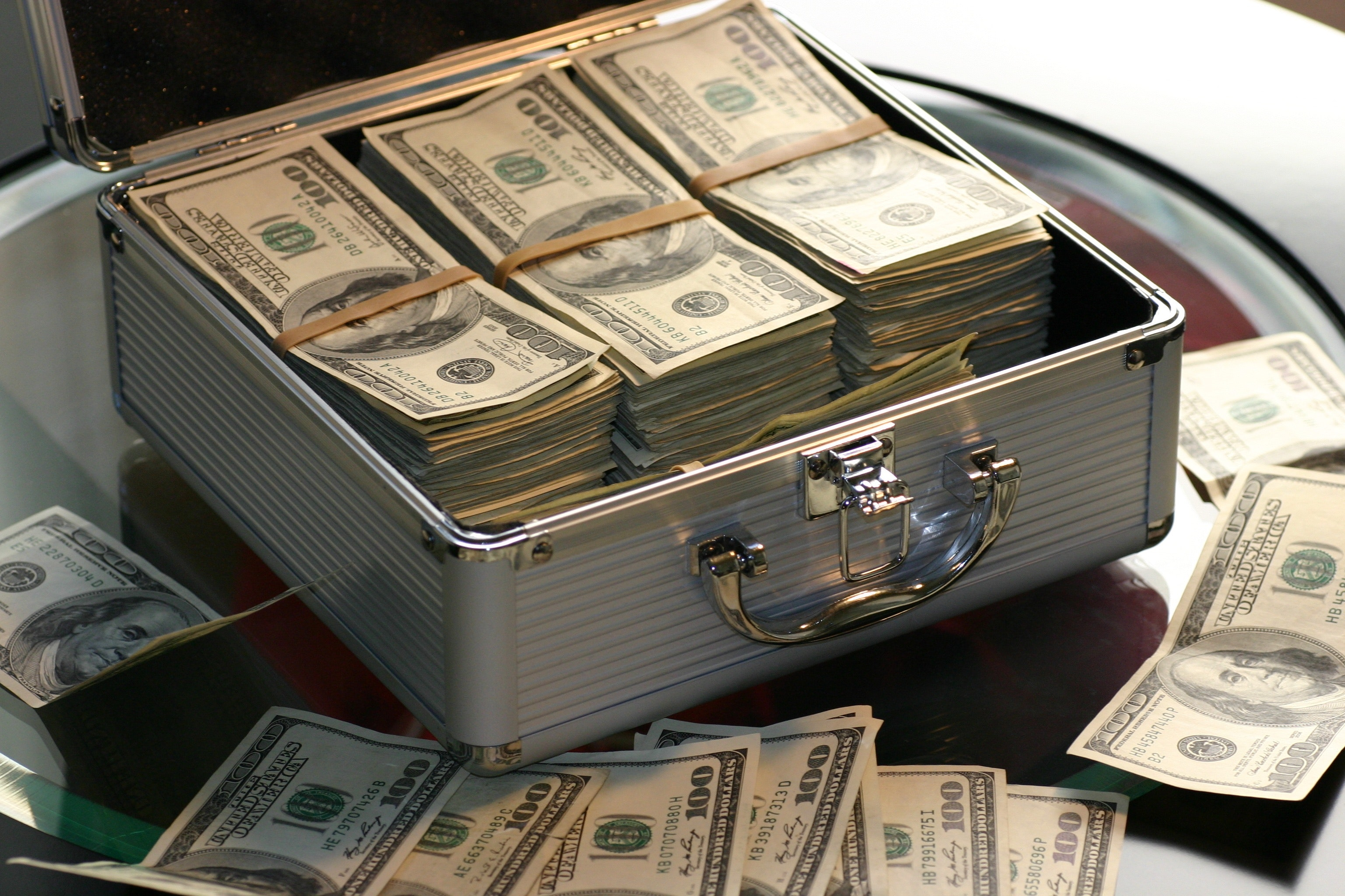 3 stacks of $100 bills wrapped in rubber bands placed in a silver briefcase.