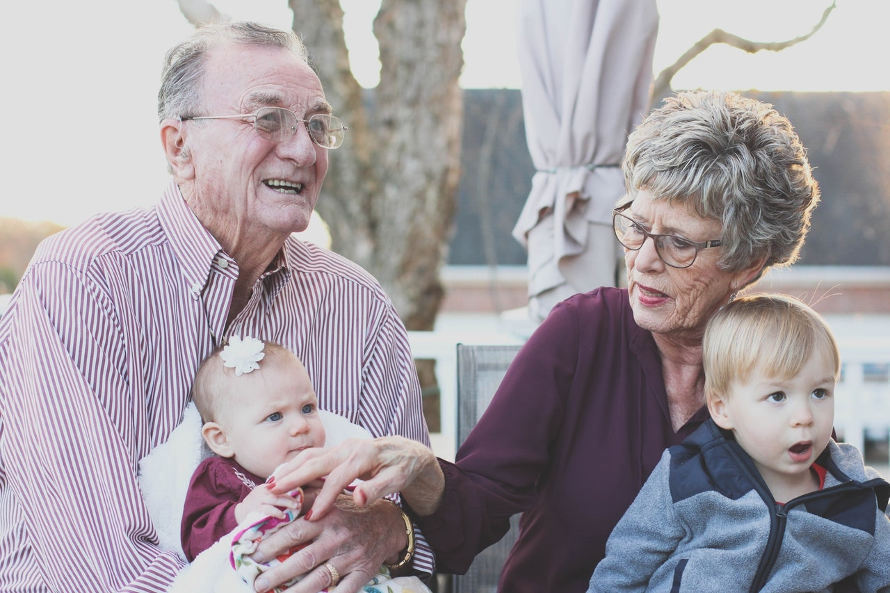 An elderly couple sitting next to each other outdoors. The man has his granddaughter in his lap. The woman has her grandson in her lap.