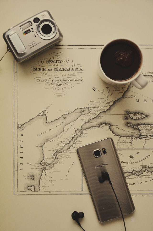 Black coffee in a mug, black ear buds, a silver smartphone, and a silver camera resting on a map.