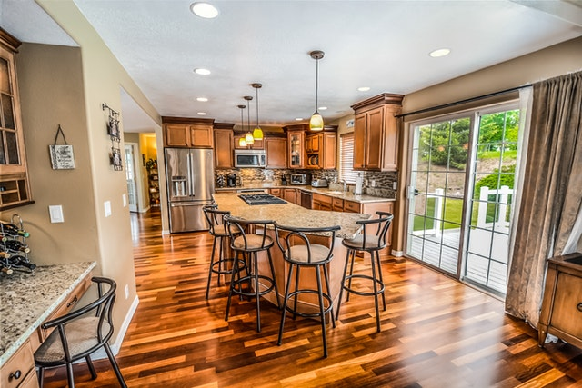 A well-furnished kitchen with wood floors, granite-top island, wood cabinets, and a sliding glass door.