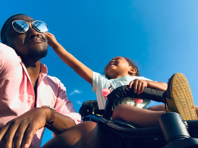 A man with sunglasses smiling and leaning on a stroller while his daughter smiles and grabs at his sunglasses.