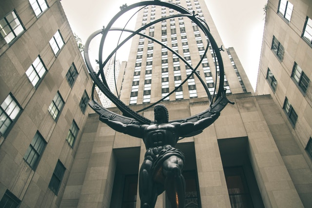 Low angle of a cast iron statue of Atlas, with the Rockefeller Center in the background.