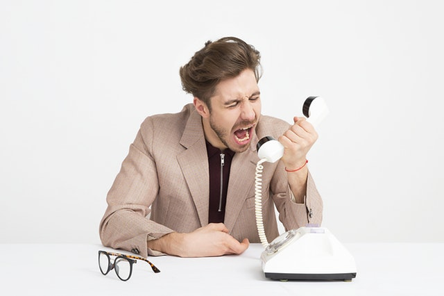 A young adult in a brown suit jacket screaming into a landline phone