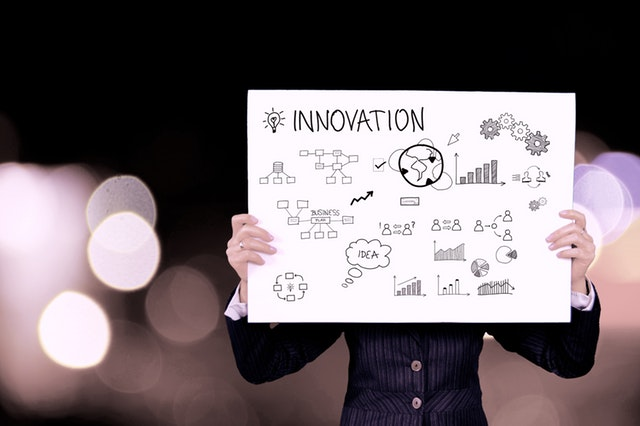 """A woman holding a flow chart titled """"Innovation"""""""