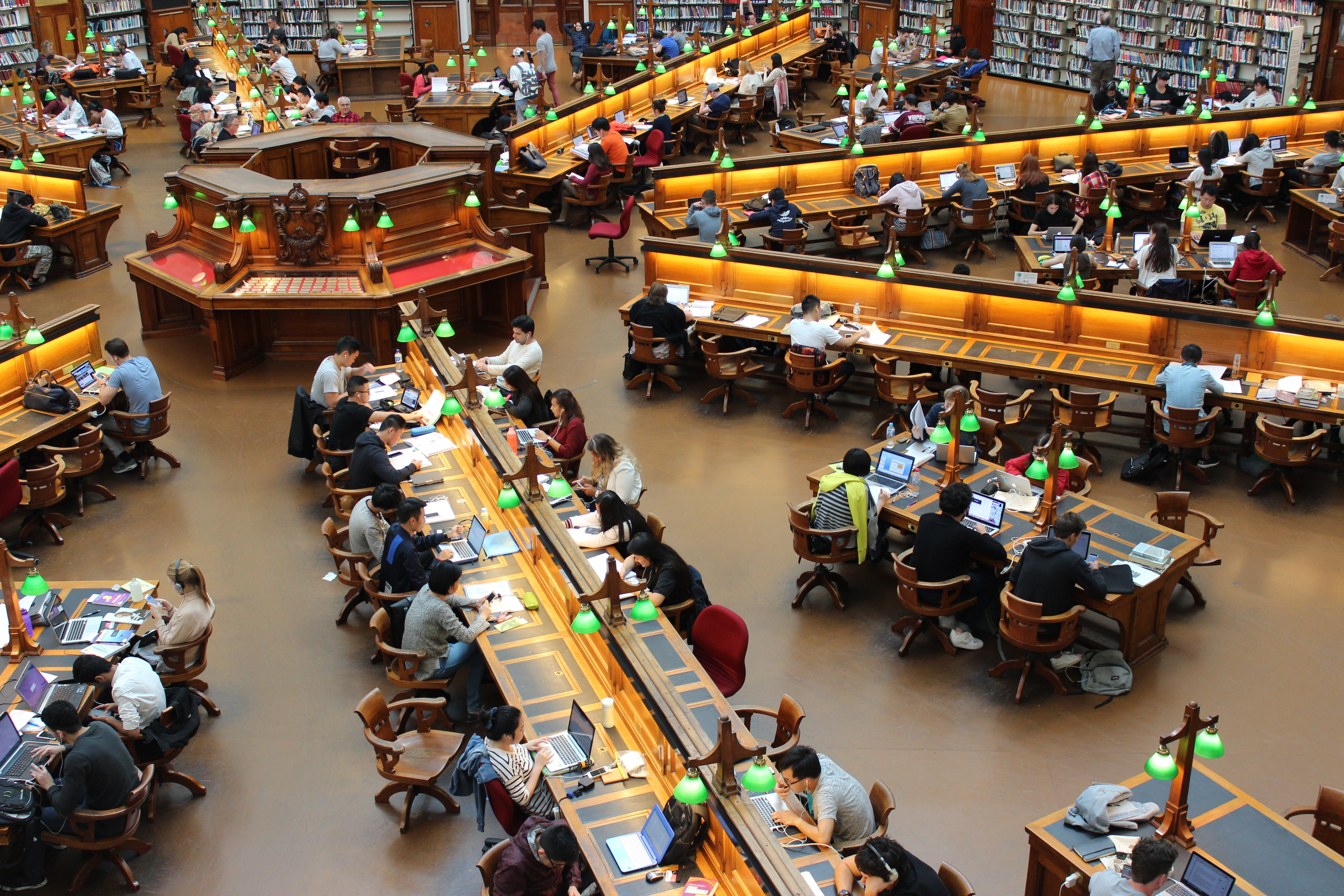 High-angle view of many people sitting at various long tables in a library