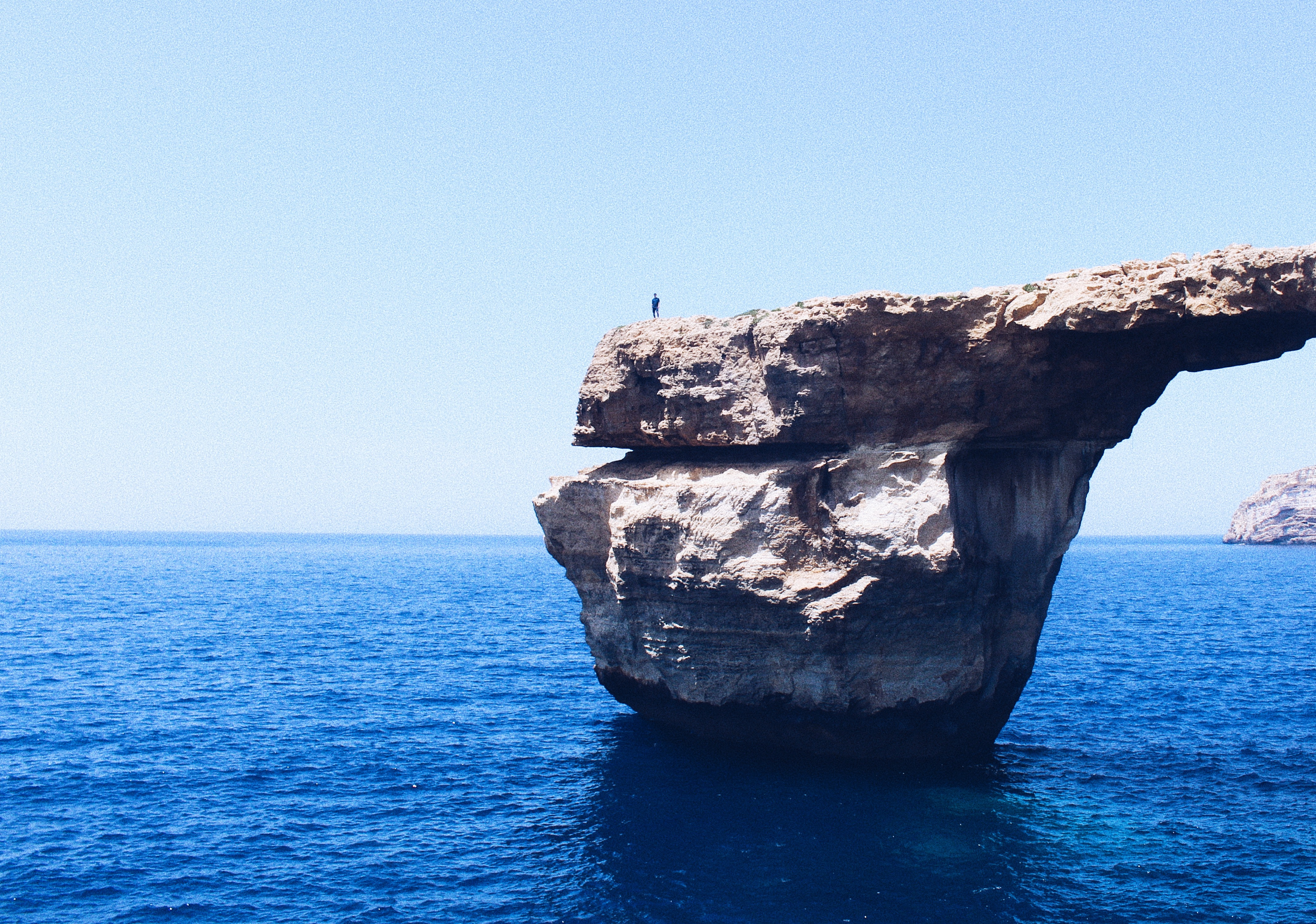 A large solitary rock in the middle of a blue body of water with a person on the edge.