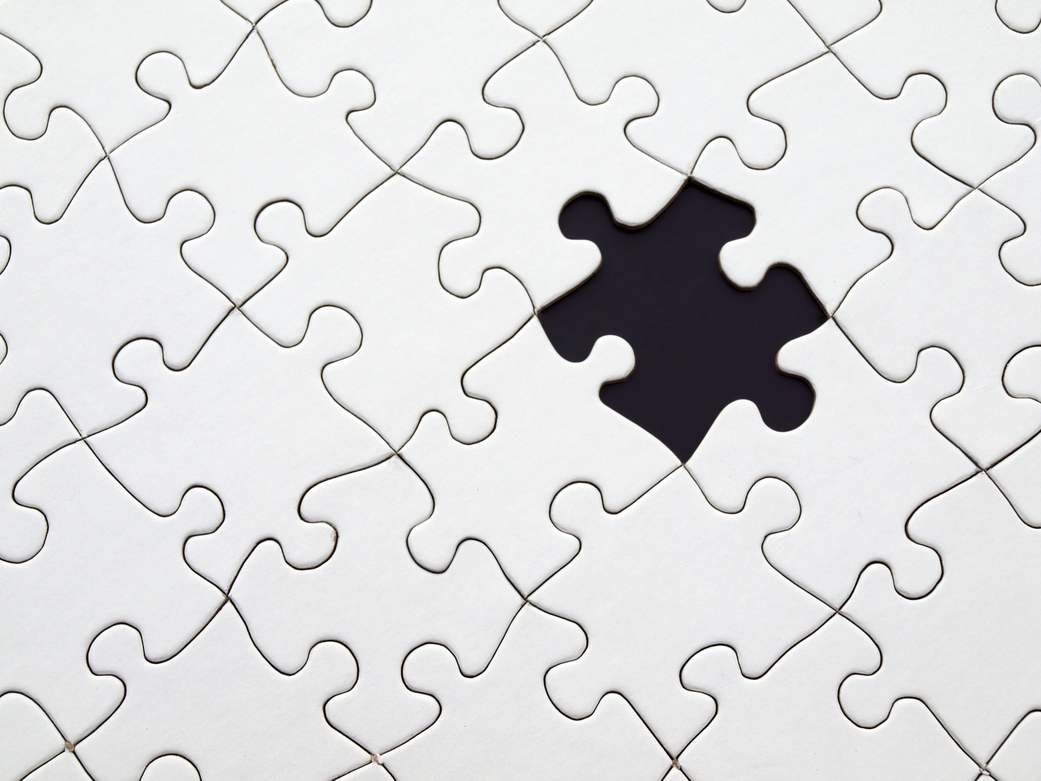 Image Of A Completed Blank Puzzle That is Missing One Puzzle Piece In The Left-Hand Corner