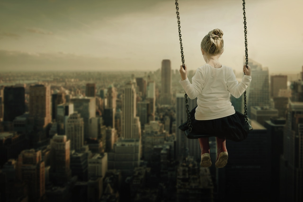 Image of Child on Swing Overlooking City