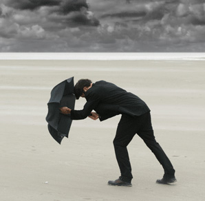Businessma Holding an Umbrella Against Headwinds