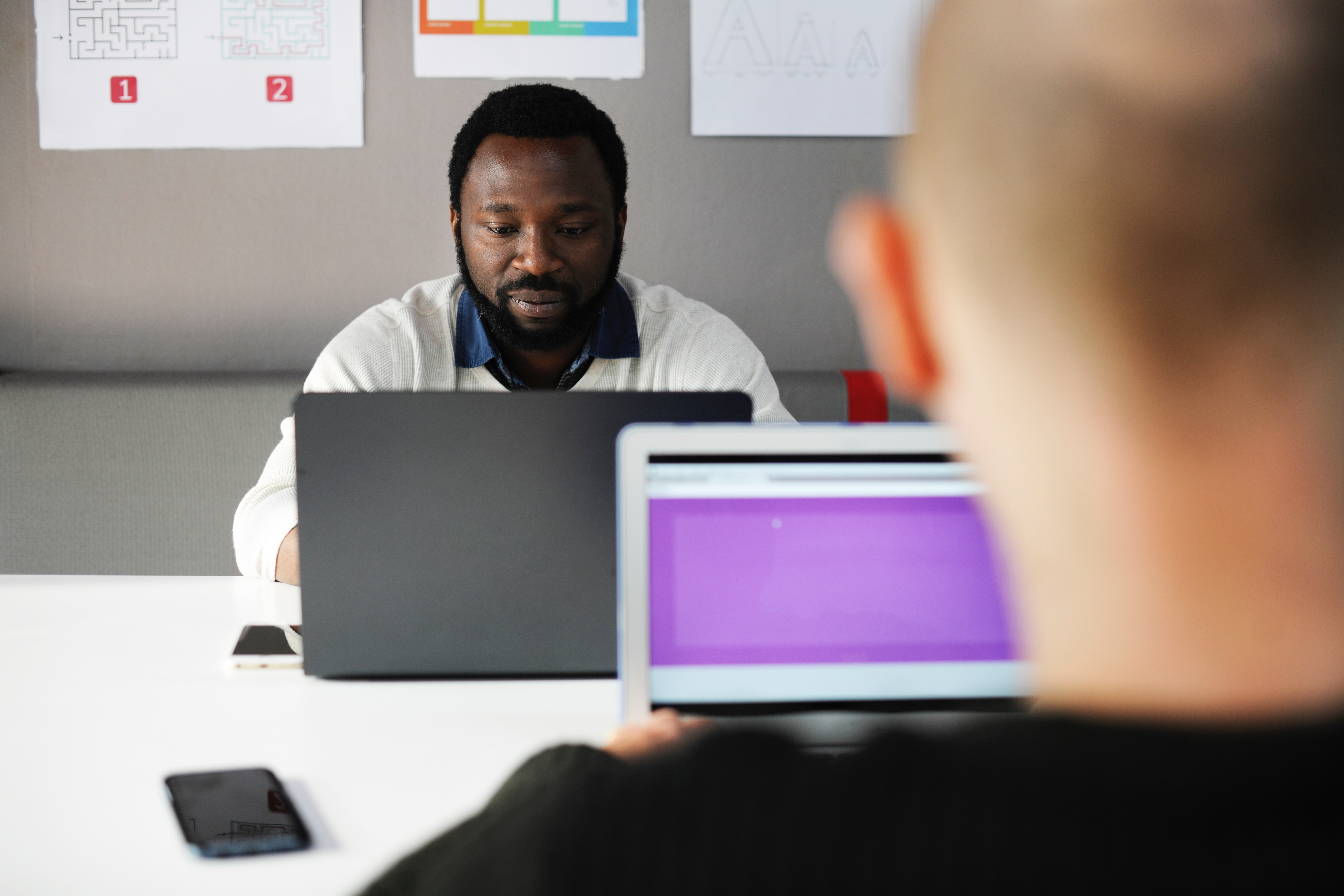 A man's face looking at a computer, with the back of a coworker's head blurred in the foreground.
