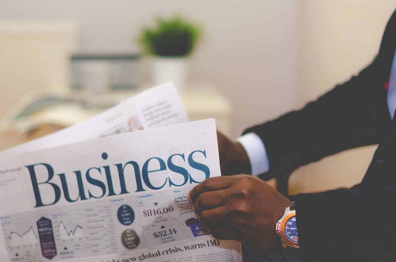 Image Of A Business Advisor Reading Business Newspaper Articles