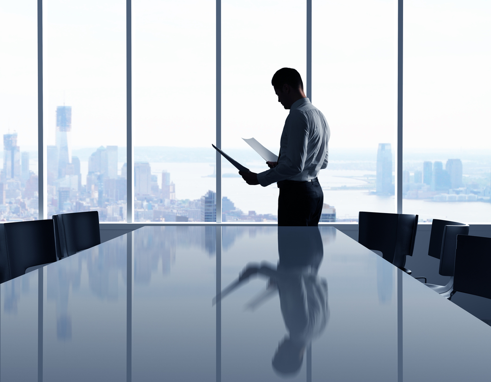 Image of a Business Owner Standing at a Conference Room Window