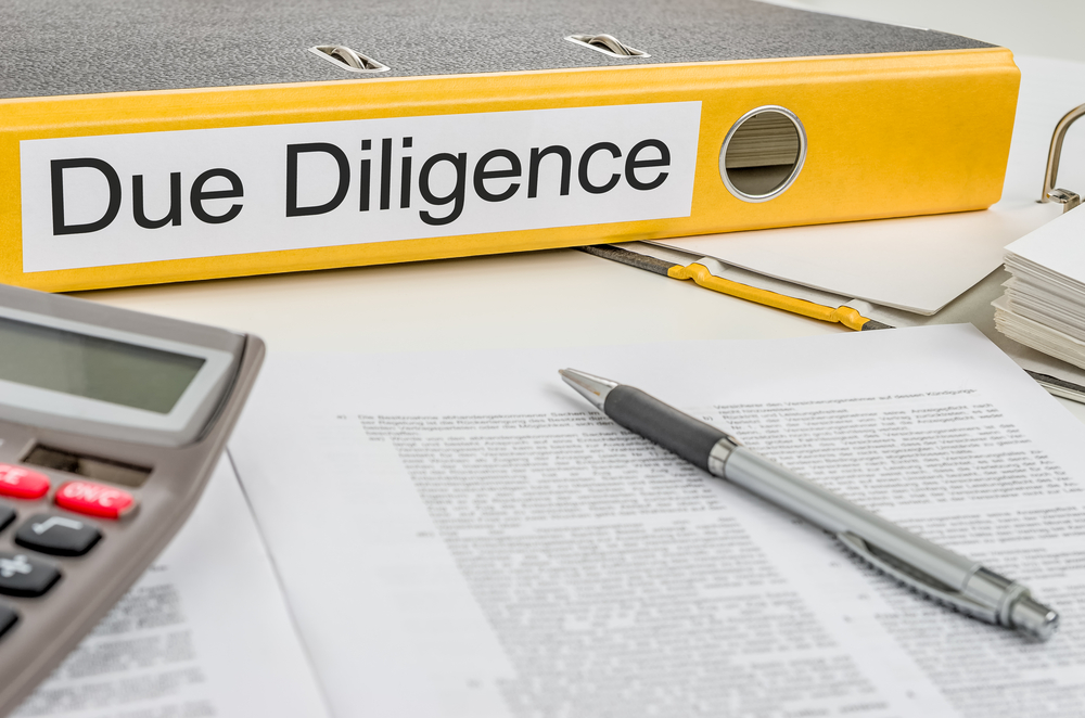 "A binder with a yellow spine that says ""Due Diligence"" on a table with a calculator, a pen, and paper."